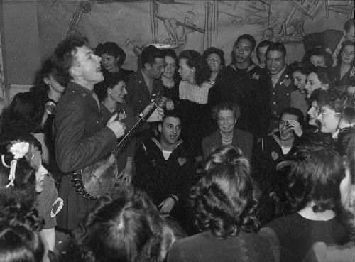 Washington, D.C. Pete Seeger, noted folk singer entertaining at the opening of the Washington labor canteen, sponsored by the United Federal Labor Canteen, sponsored by the Federal Workers of American, Congress of Industrial Organizations (CIO), photo by Joseph A. Horne, 1944