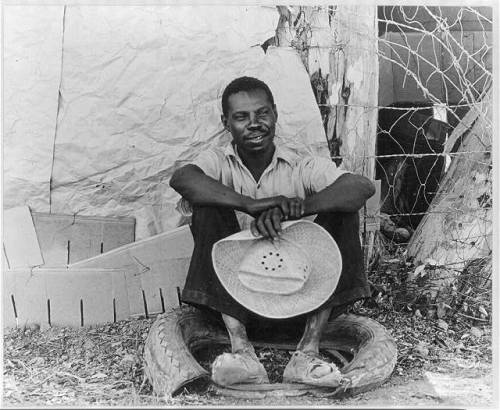 Negro field worker. Holtville, Imperial Valley, California. He has just made himself shoes out of that old tire, photo by Dorothea Lange, 1935.