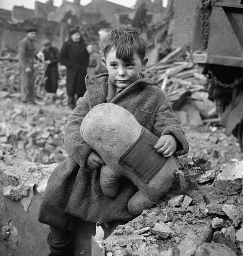 [Abandoned boy holding a stuffed toy animal amid ruins following German aerial bombing of London, by Toni Frissell, 1945
